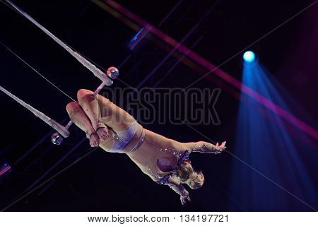 ST. PETERSBURG, RUSSIA - JUNE 2, 2016: Trapeze artist Olga Shmeleva in the dress rehearsal of the Show of Water, Fire, And Light in Ciniselli circus. This new show first time arrived in St. Petersburg