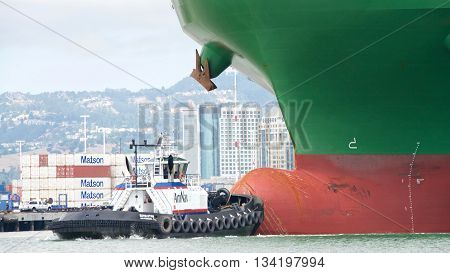 Oakland CA - June 09 2016: Tugboat REVOLUTION at the bow of cargo ship CSCL WINTER assisting the vessel to maneuver into the Port of Oakland. Tugboats are powerful for their size and strongly built
