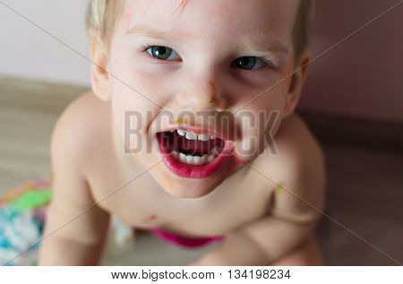 Closeup portrait of little screaming girl. Photo at home.