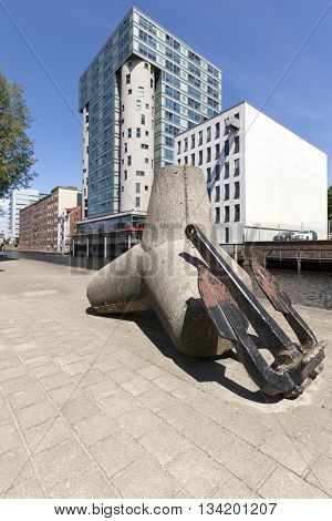 Silo building at the harbor of Hamburg-harburg, old breakwater tetrapod and anchor in foreground