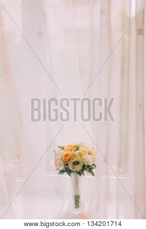 Beautiful bouquet of pale white and orange roses in cut glass vase on windowsill. Bright window with white curtains at background