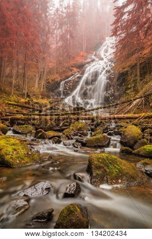waterfal with rocks and trees in autumn with mist