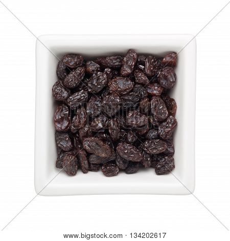 Raisins in a square bowl isolated on white background