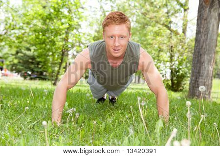 Man doing a push up in park