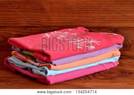 Mix long sleeve tops for girls. Stack of colorful cotton children clothing on wooden background. How to store baby and kid clothes