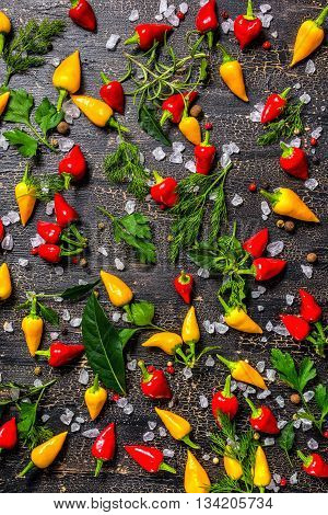 Flat Lay Of Decorative Spices, Dry Peppers, Sea Salt, Different Greenery On Cracks Black Background,