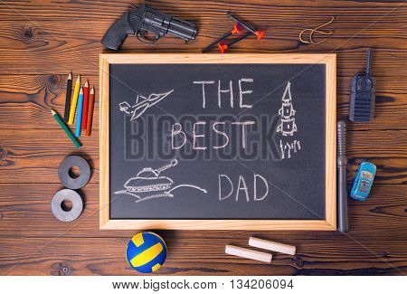 Concept Of Father's Day With Handwritten Text The Best Dad, Pictured Airplane, Tank, Rocket On Black