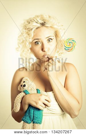 Blonde girl with wide open eyes holding colorful lollipop in one hand and bear toy in other hand.
