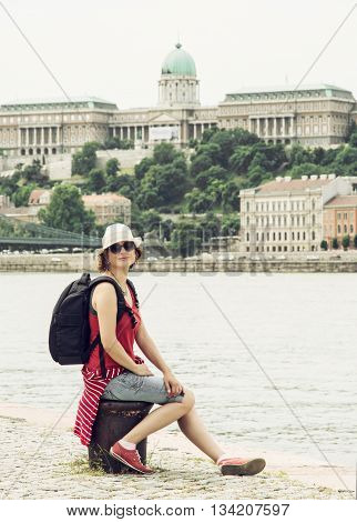 Joyful tourist woman posing with Buda castle on the Danube river bank in Budapest Hungary. Travel destination. Cultural heritage. Architectural theme. Traveler's enthusiasm. Vertical composition.