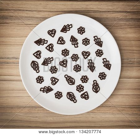Dark chocolate garnishes in the big plate. Sweet food. Symbolic shapes. Creative cuisine. Confection theme.