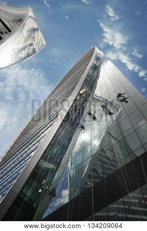 Moscow Russia - June 10 2016: Cleaning windows on the side of a high rise building. Moscow City. View of skyscrapers Moscow International Business Center.