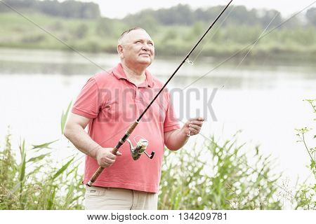 Middle aged man wearing polo shirt, setting up bait during summer angling in rain on lake - fishing concept