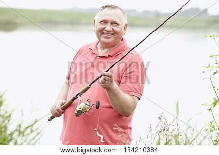 Portrait of smiling middle aged man wearing polo shirt, angling with rod and spinning reel on summer lake - fishing concept