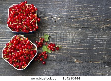 Fresh red currant on dark wooden table