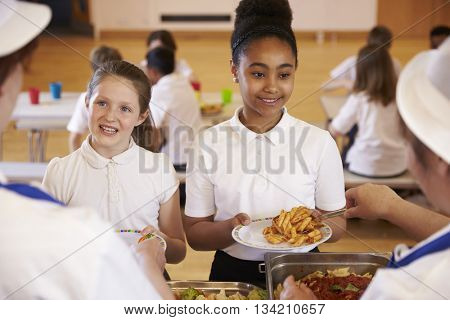 Over shoulder view of girls being served in school cafeteria