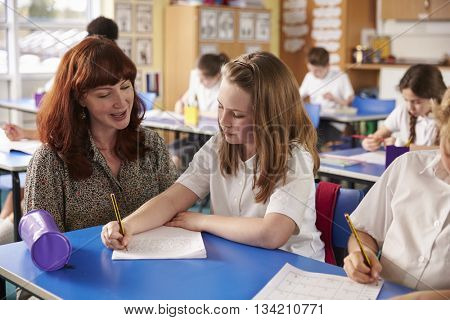 Primary school teacher helping a girl writing at her desk
