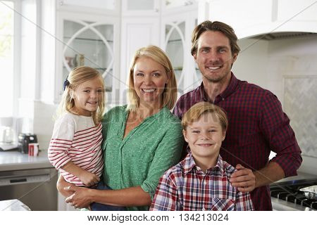 Portrait Of Family Standing In Kitchen Together