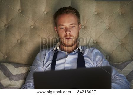Businessman At Home On Bed Working Late On Laptop