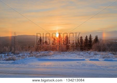 tracks on road with ice and snow in a forest mountain landscape with rainbows from a candle like sun