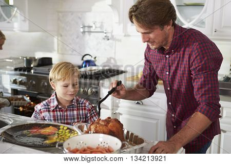 Father And Son Preparing Roast Turkey Meal In Kitchen