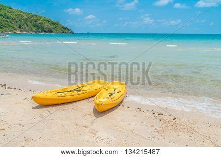 Yellow kayaks on white sand beach