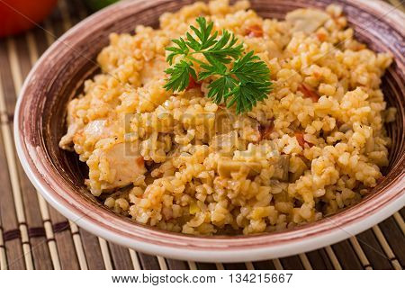 Spicy bulgur with mushrooms and chicken. Close up