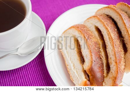 Sweet roll with apple stuffing and cup of tea