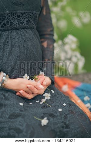 sitting in a lace dress. pregnant women with flowers.