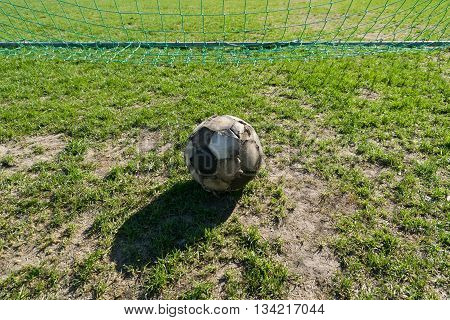 Old ragged soccer ball on grass in front of gate.