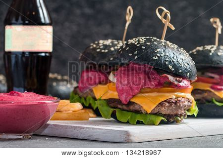 Gourmet black burger with berry sauce, french fries and drink on wooden table and dark background