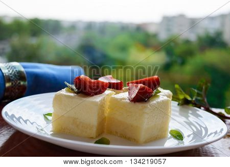Delicate cottage cheese and creamy souffle in the form of cubes decorating with mint leaves and fresh strawberries on a white plate on a background of nature