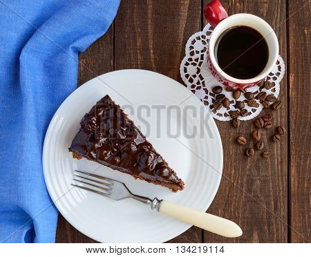Chocolate and cherry cake. A piece on a white plate close-up. A cup of coffee. The top view.
