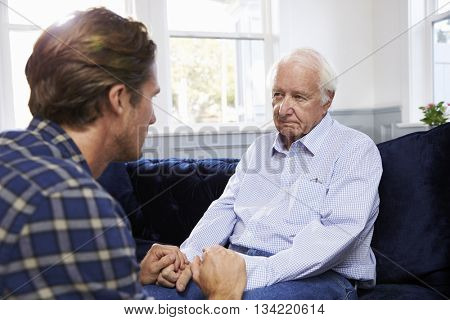 Adult Son Talking To Depressed Father At Home