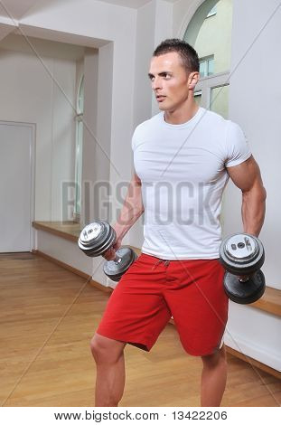 Powerful and sexy muscular man lifting weights