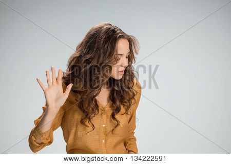 The young woman's portrait with frightened emotions on gray background. She pushing something with hand