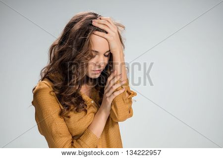 The young woman's portrait with sad emotions on gray background.