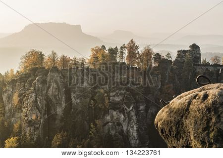 Bastei bridge in Saxon Switzerland in autumn Germany. In the background mesas Lilienstein and Konigstein.