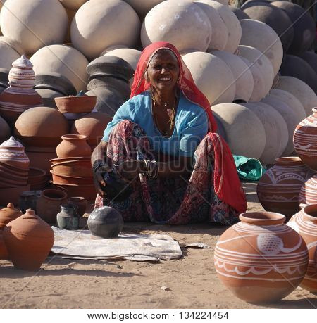 RAJASTHAN, INDIA: MARCH 2016. An unidentified smiling Indian woman in typical clothes and jewellery of that northwestern state of India sits on the ground selling the big round clay pots traditionally used to carry water.