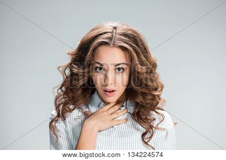 The young astonished woman on gray background