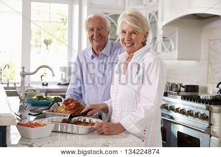 Senior Couple Make Roast Turkey Meal In Kitchen Together