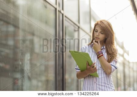 Young beautiful business woman on a break walking next to an office building pensive