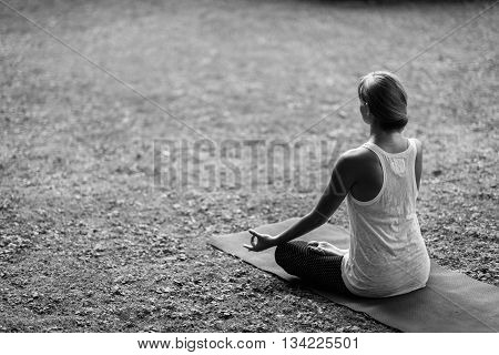 Beautiful relaxed young woman doing Yoga sitting in half lotus position