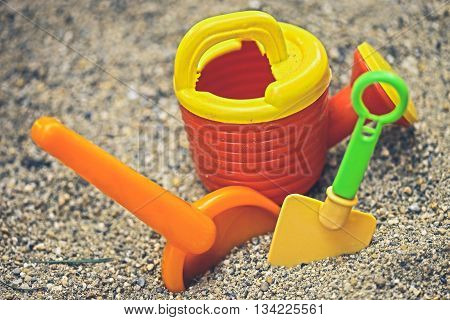 Red orange green and yellow plastic toys in sand playground