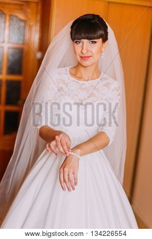 Beautifal bride in gorgeous white dress showing her pearl bracelet, while dressing before ceremony.
