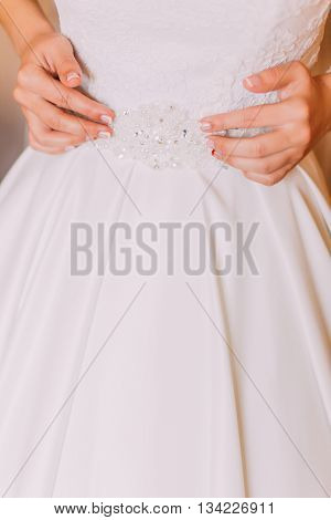 Dressing beautiful wedding dress on before marriage ceremony.