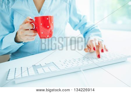 Female hands or woman office worker typing on the keyboard and drinking coffee