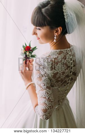 Thoughtful young bride posing with cute floral boutonniere near the window before wedding ceremony.