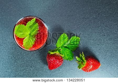 fresh strawberries and juice with pulp in a glass with green leaf on gray stone background. focus on the juice