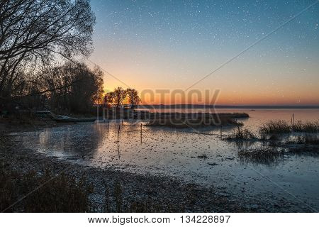The frozen winter coast in the evening on a decline and with stars against the sky. Elements of this image furnished by NASA.
