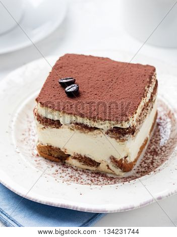 Tiramisu traditional Italian dessert on a white plate